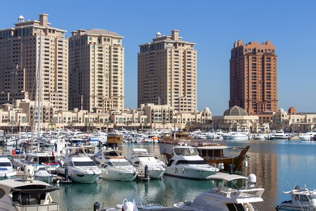 DOHA, QATAR - DECEMBER 25, 2017 : Harbour view in the Pearl precinct of Doha, Qatar, with yachts, boats and buildings under construction in the background