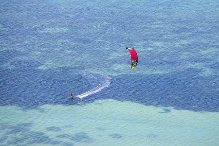 KOH PHANGAN, THAILAND - MARCH 02, 2018 : Young man kitesurfing in ocean, extreme summer sport on the island Koh Phangan, Thailand Stock Photo - 110649723