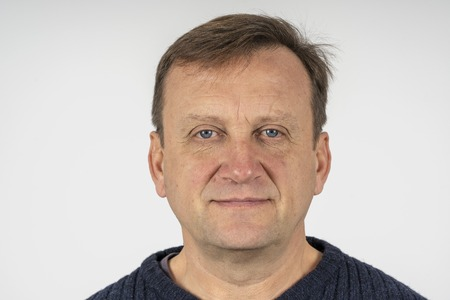 Portrait of a middle-aged man against a white wall background, close up. Photo on document Stockfoto