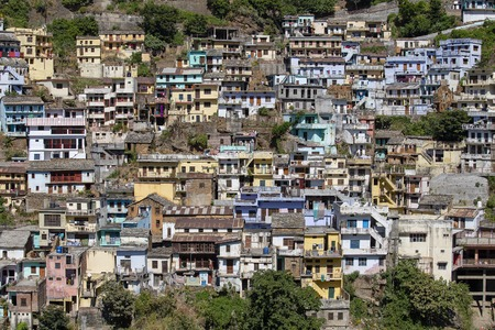 Colorful houses on the mountainside in Devprayag, India. Devprayag is the last prayag of Alaknanda River and from this point the confluence of Alaknanda and Bhagirathi River is known as Ganga, India