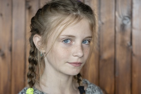 Beautiful blond young girl with freckles indoors on wooden background, close up portrait