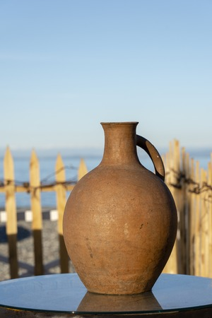 Large earthenware jug stands on a table on the shore near the sea water in Batumi, Georgia. Close up Stock fotó