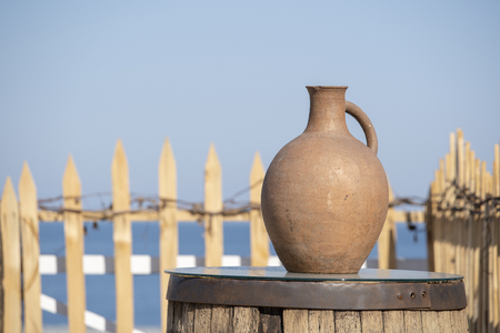 Large earthenware jug stands on a table on the shore near the sea water in Batumi, Georgia. Close up Foto de archivo