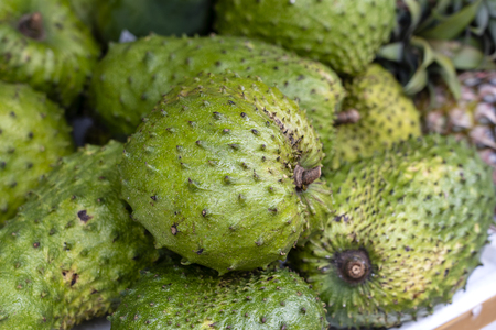 Soursop, Guanabana or Custard Apple or Annona muricata and green coconut on street market in Ubud, island Bali, Indonesia. Close up Foto de archivo