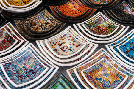 Colorful mosaic decorative plates on the market for sale on local street market in Ubud, island Bali, Indonesia, close up . Souvenirs for tourist