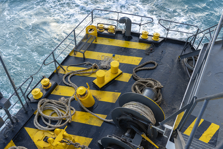 Yellow and black painted ferry deck boat along with the a thick mooring rope and blue sea water wave, Thailand. Close up Banque d'images
