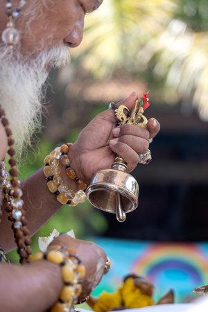 UBUD, BALI, INDONESIA - APRIL 22, 2019 : Ida Pedanda Gede Made Gunung a Hindu high priest, conducts religious prayer during Bade cremation ceremony on central street in Ubud, Island Bali, Indonesia Editorial