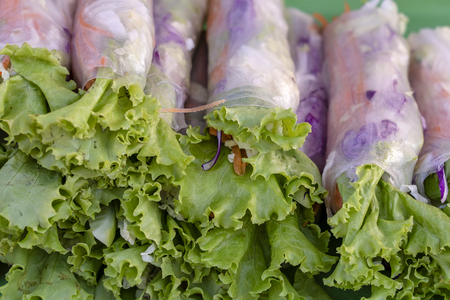 Wrapped rice noodles, green lettuce leaf, carrot and blue cabbage, close up. Fresh rolls with rice noodles wrapped in lettuce and rice paper with herbs, Thai cuisine, popular food in Thailand Zdjęcie Seryjne - 121622333