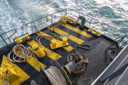 Yellow and black painted ferry deck boat along with the a thick mooring rope and blue sea water wave, Thailand. Close up