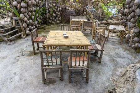 Wooden table and chairs in empty beach cafe next to sea in garden. Close up. Island Koh Phangan, Thailand