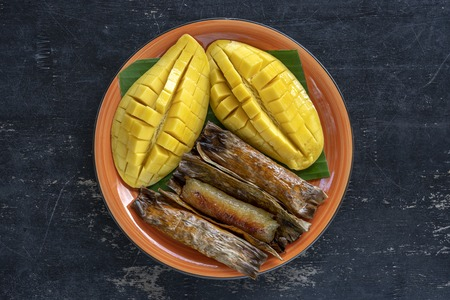 Thai style dessert, yellow mango with banana sticky rice in palm leaves. Yellow mango and sticky rice is popular traditional food of Thailand. Close up