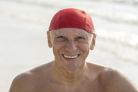 Happy elderly man in a red swimming hat on the beach near the sea water 写真素材