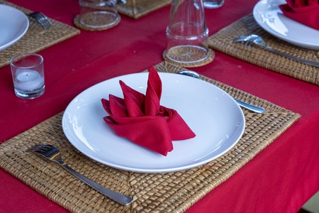 Elegant table setting with fork, spoon, white plate and red napkin in restaurant , close up. Nice dining table set with arranged silverware and napkins Imagens