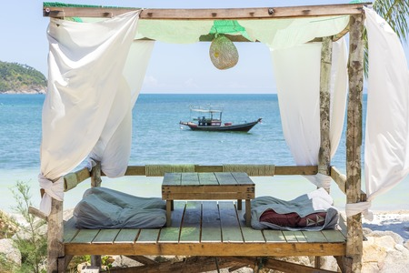 Gazebo for relaxing with white curtains on tropical sand beach near blue sea water on the island Koh Phangan, Thailand
