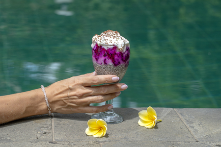 Girl hand holding a glass with hia seeds pudding on the background of the swimming pool water, close up. Chia seeds pudding with red dragon fruit and white yogurt in a glass for breakfast