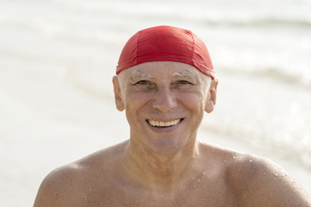 Happy elderly man in a red swimming hat on the beach near the sea water Banco de Imagens