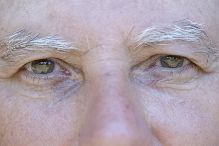 Nahaufnahme Auge des kaukasischen alten Mannes. Porträt des alten Mannes draußen. Kaukasischer männlicher Gesichtshintergrund, Nahaufnahme der Augen, Makro