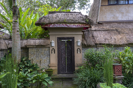 The sidewalk leads to a enter in house with Balinese sculptures in a tropical garden, Ubud, island Bali, Indonesia 版權商用圖片