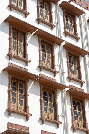 White wall with windows decorated in Indian style in Pushkar, Rajasthan, India. Background of Indian architecture. Close up
