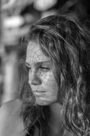 Black and white portrait of a beautiful caucasian girl on a tropical beach with a web shadow, Thailand, close up. Nature and summer concept