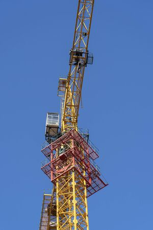 Yellow crane and blue sky on building site, close up Imagens