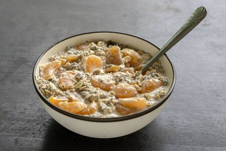 Bowl with muesli and yogurt with banana, mandarin, chia seeds and oat cereals, healthy food concept, close up