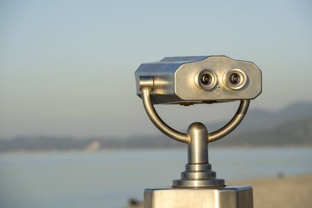 Public binocular on sea shore, close up. Coin operated binocular viewer on blurred background of sunset and sea. Batumi, Georgia