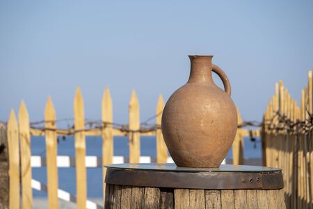 Large earthenware jug stands on a table on the shore near the sea water in Batumi, Georgia. Close up Stock Photo