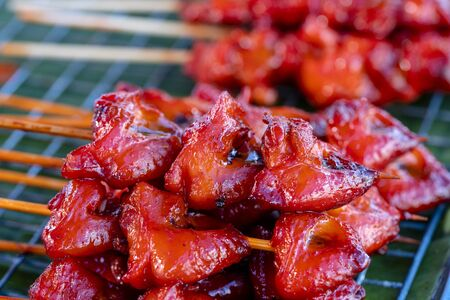 Thai street vendor sells grilled chicken meat at street food market in island Koh Phangan, Thailand. Close up