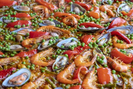 Spanish seafood paella in fry pan with mussels, shrimps and vegetables. Seafood paella background, close up, traditional spanish rice dish Imagens