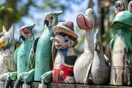 Old wooden souvenirs toys on the stone fence near the doll shop in Ubud, Bali island, Indonesia. Close up