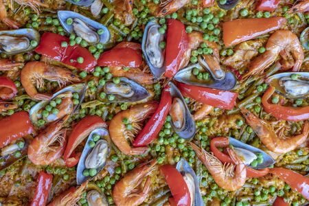 Spanish seafood paella in fry pan with mussels, shrimps and vegetables. Seafood paella background, close up, traditional spanish rice dish Stok Fotoğraf
