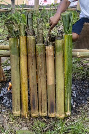 Burning bamboo rice in traditional cooking, asian food. Ubud, island Bali, Indonesia . Close up. Burned sticky rice with sweet coconut milk in bamboo shot Stok Fotoğraf