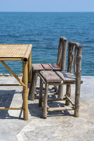 Bamboo table and wooden chairs in empty cafe next to sea water in tropical beach. Close up. Island Koh Phangan, Thailand