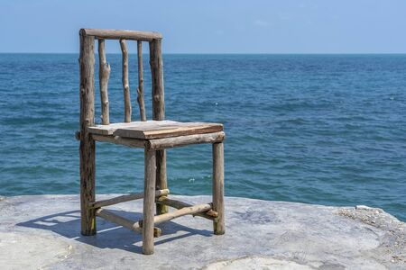 Wooden chair in empty cafe next to sea water in tropical beach. Close up. Island Koh Phangan, Thailand