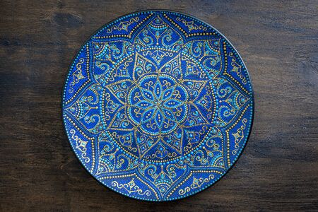 Decorative ceramic plate with blue and golden colors, painted plate on wooden background, close up. Decorative porcelain plate painted with acrylic paints, handwork Standard-Bild