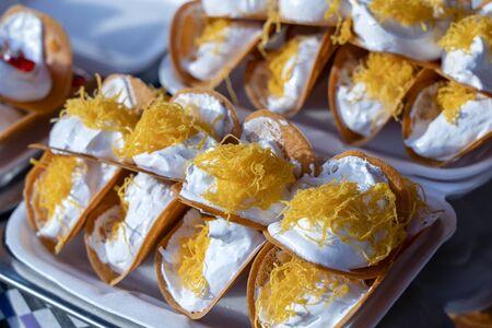 Leckeres thailändisches Straßendessert, Kanom Buang, Thai Crispy Pancake oder Thai Cr Crepe, mit verschiedenen Füllungen wie süßer weißer Vanillepuddingcreme und goldener süßer Eierseide oder salzig gehackter Garnele auf Bratpfanne