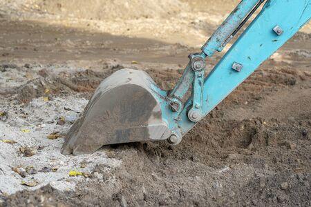 Excavator bucket on the ground, industrial excavator machine. Close up
