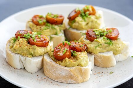 Homemade toast sandwich with avocado, cherry tomato and green dill on white bread, healthy food concept for breakfast, close up