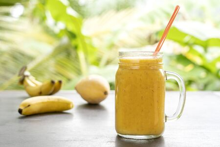 Smoothie with tropical fruits: mango, banana, pineapple in a glass jar on the wooden table. The concept of a healthy lifestyle. Close up. Healthy yellow smoothie, banana and mango cocktail