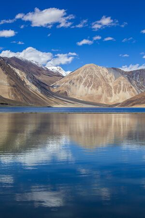 View of majestic rocky mountains against the blue sky and lake Pangong in Indian Himalayas, Ladakh region, Jammu and Kashmir, India. Nature and travel concept Stock Photo