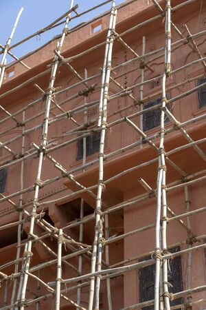 Bamboo scaffold on house, renovation. Scaffolding on building, pink wall and window. Scaffolding system in construction. Jaipur, India Stockfoto