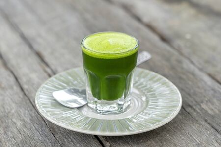 Wheat grass juice natural drink with fresh wheatgrass in glass on old wooden table background. Green organic healthy organic green detox juice, close up