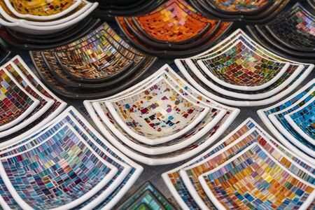 Colorful mosaic decorative plates on the market for sale on local street market in Ubud, island Bali, Indonesia, close up. Souvenirs for tourist