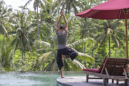 Man doing yoga and meditating in tree position near swimming pool water on the tropical beach in island Bali, Indonesia. The concept of a healthy lifestyle