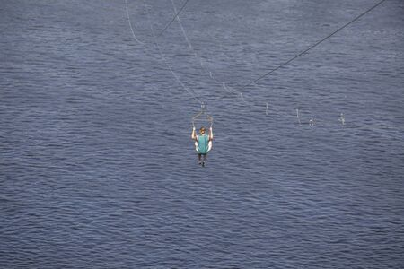 Rear view of young woman riding on zip line against a background of a blue river water wave, Kyiv, Ukrainee
