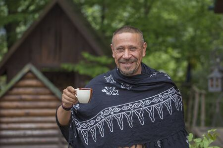 People and lifestyle concept. Happy middle-aged man with cup coffee outdoor against green nature background, portrait. Adult man portrait close up Imagens