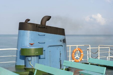 Smoke from ferry boat flue during sea with sunlight, sea water and blue sky in background, Thailand. Aboard, chimney of a ferry or cruise ship, smokestack pollutes the atmosphere Standard-Bild