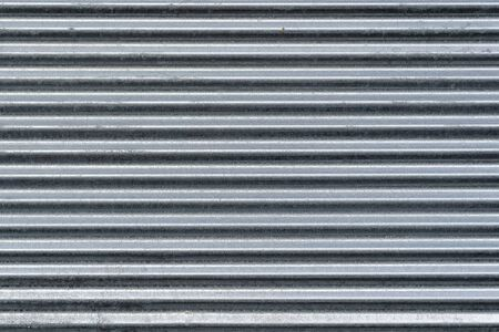 Metal wall texture, background. Sheet of ribbed galvanized metal for building structures. Surface has horizontal protruding ribs for stiffness. It is used for covering roofs for construction of fences