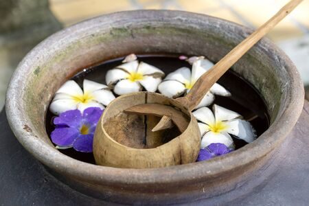 Scoop coconut shell and an earthenware jar filled with water together with flowers. Thailand. Close up